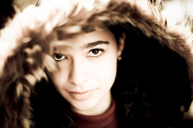 Adolescente serio in cappotto con cappuccio bordato di pelliccia