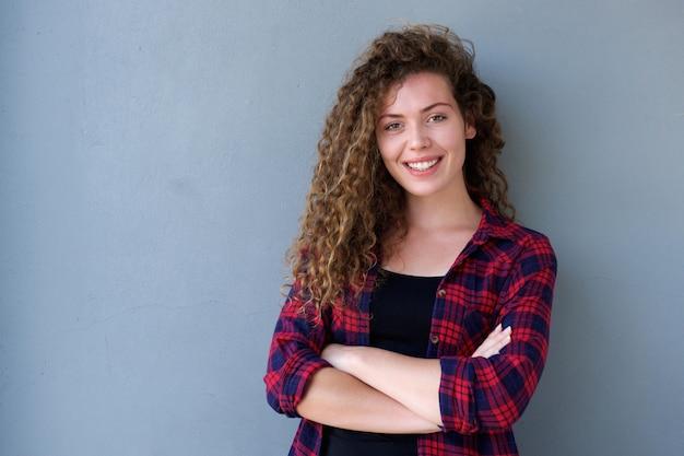 Adolescente sorridente che si leva in piedi con le braccia attraversate