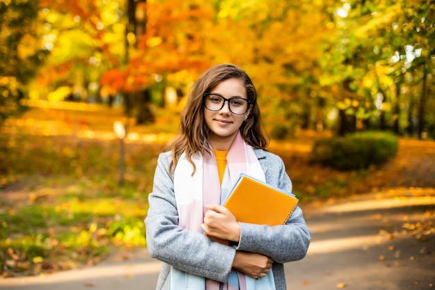 Adolescente sorridente felice del ritratto all'aperto di autunno con i quaderni