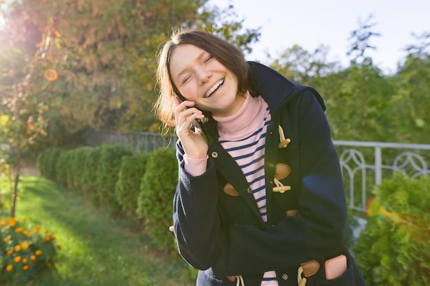 Adolescente sorridente felice in cappotto che parla sul telefono cellulare