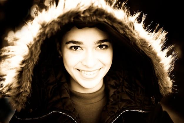 Adolescente sorridente in cappotto con cappuccio bordato di pelliccia