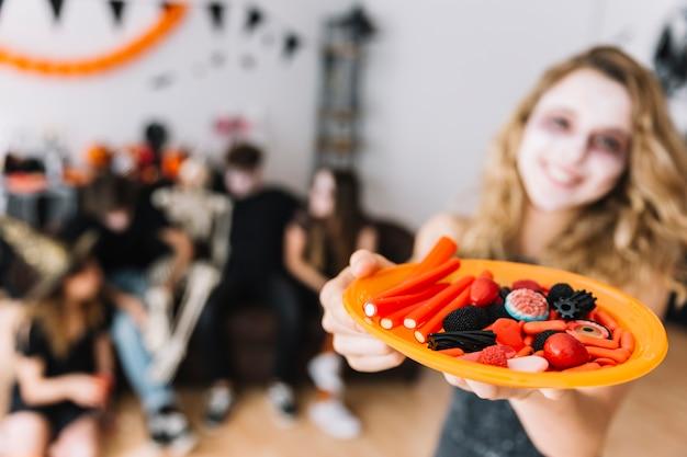 Adolescente sulla festa di halloween che dà zolla con la marmellata d'arance