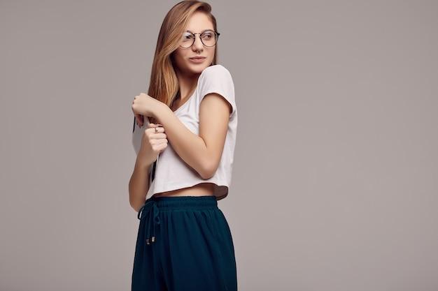 Adolescente sveglio in camicia bianca e vetri che tengono compressa digitale