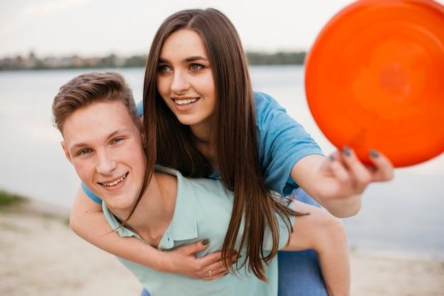 Adolescenti a tiro medio con frisbee rosso