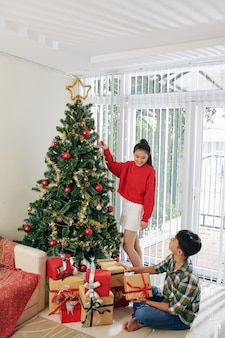 Adolescenti che decorano l'albero di natale