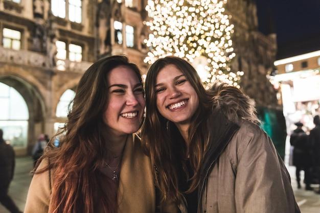 Adolescenti e amici che sorridono con l'albero di natale