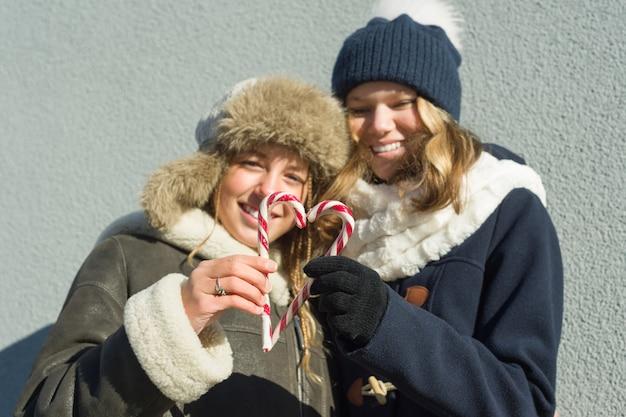 Adolescenti graziosi sorridenti felici con i bastoncini di zucchero di natale