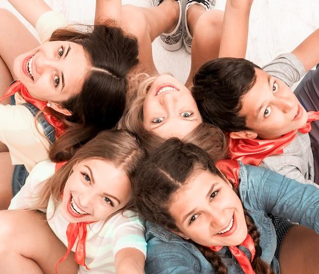 Adolescenti seduti sul pavimento con le mani in alto