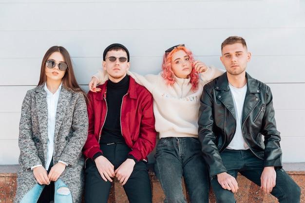 Adolescenti seri ed eleganti che si siedono sul banco sulla via