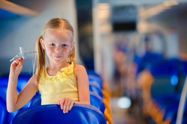Adorabile bambina che viaggiano in treno e divertirsi con il modello di aeroplano in mano