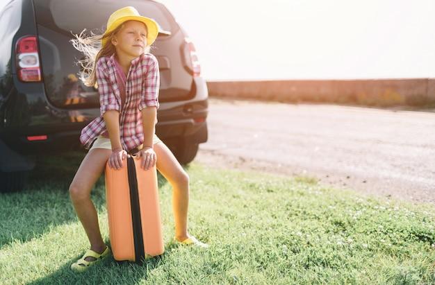 Adorabile bambina con una valigia in partenza per una vacanza in auto con i loro genitori