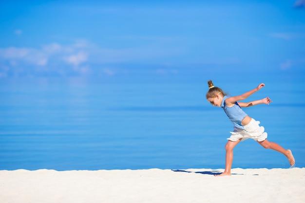 Adorabile bambina durante le vacanze al mare divertendosi