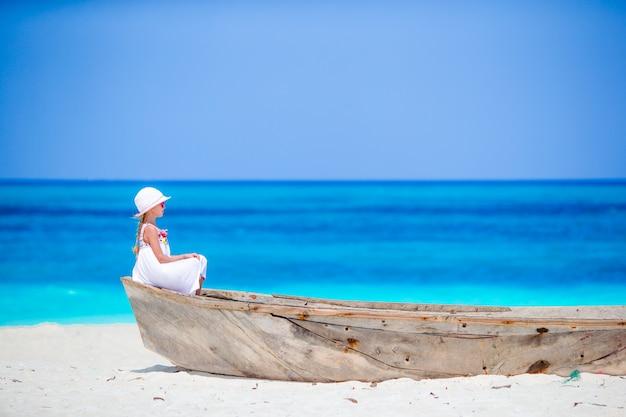 Adorabile bambina in barca sulla riva