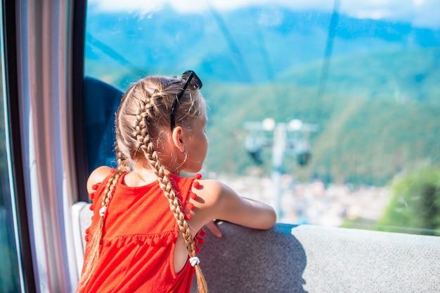 Adorabile bambina in cabina sulla funivia