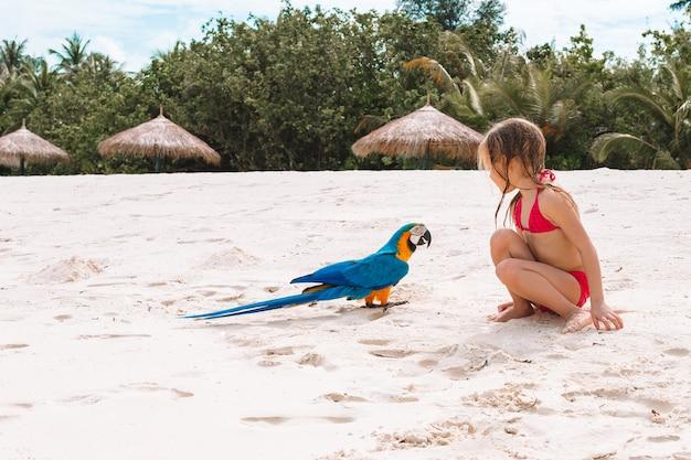 Adorabile bambina in spiaggia con pappagallo colorato