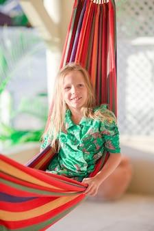 Adorabile bambina in vacanza tropicale rilassante in amaca