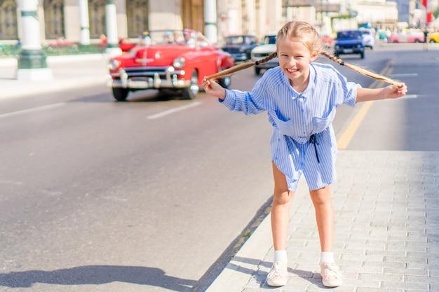 Adorabile bambina nella zona popolare di l'avana vecchia, cuba. ritratto di bambino, auto d'epoca classica americana