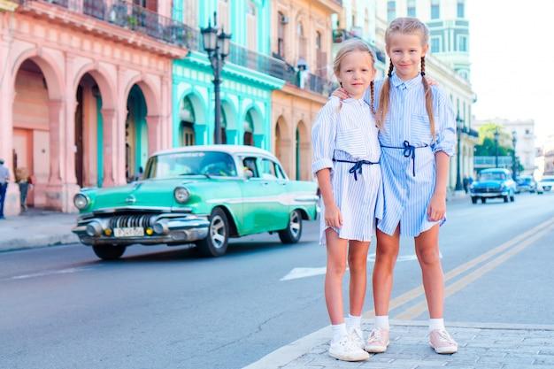Adorabile bambina nella zona popolare di l'avana vecchia, cuba. ritratto di due bambini all'aperto su una strada dell'avana