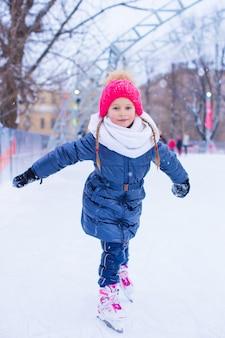 Adorabile bambina pattinaggio sulla pista di pattinaggio