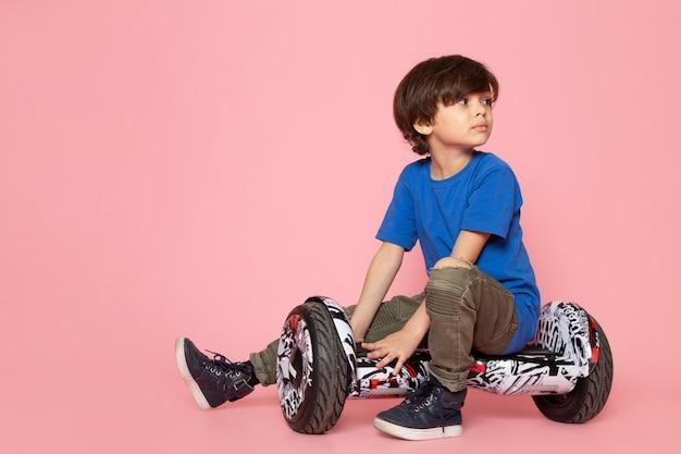 Adorabile bambino adorabile in maglietta blu cavalcando segway sulla parete rosa