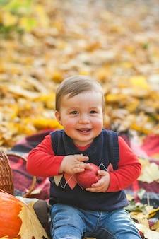 Adorabile bambino con una mela ridendo