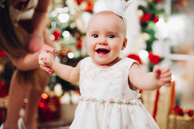 Adorabile bambino felice in abito bianco festivo a natale