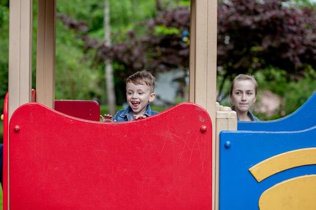 Adorabile bambino giocando su uno scivolo in un parco giochi all'aperto per bambini seduti in cima con un'espressione pittoresca mentre si prepara a scivolare giù
