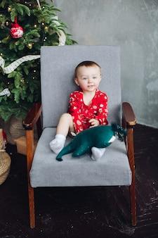 Adorabile bambino in abito rosso con stampa di natale seduto in poltrona.
