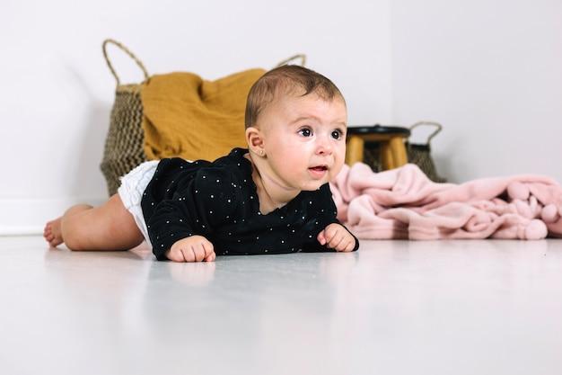Adorabile bambino sdraiato sul pavimento