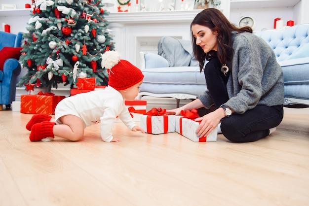 Adorabile bambino sorridente che striscia sul parquet per i regali di natale vicino a sua madre che si siede sul pavimento.
