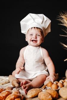 Adorabile bambino sul tavolo con pasta