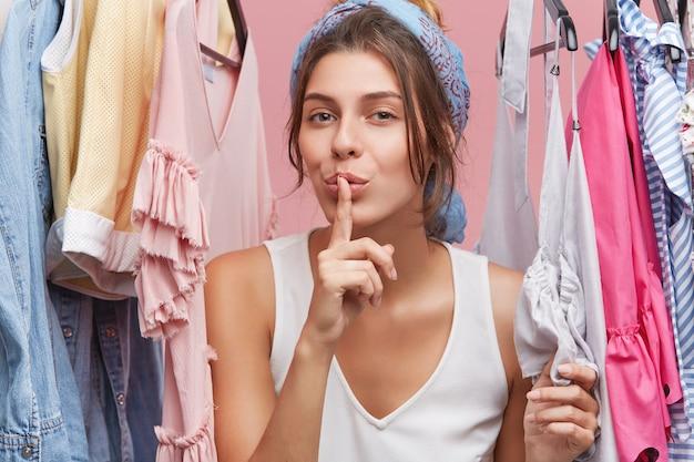 Adorabile donna in abiti casual, mostrando il segno del silenzio in piedi vicino al guardaroba con i vestiti, dimostrando cospirazione. donna che sceglie i vestiti alla moda sui ranghi. concetto di bellezza e moda