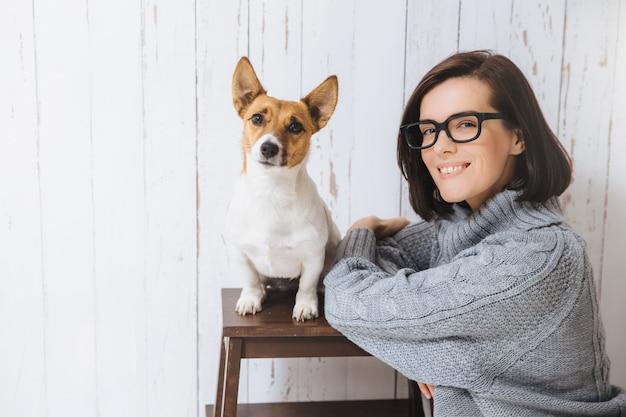 Adorabile donna soddisfatta felice indossa occhiali e maglione caldo sciolto