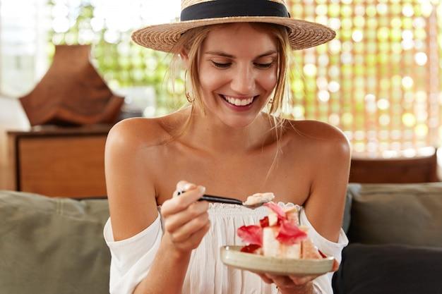 Adorabile femmina con pelle sana e sorriso positivo, mangia una gustosa torta e si siede su un comodo divano, ha un'espressione felice alla festa di compleanno di un amico. la giovane donna sveglia gode del dessert dolce