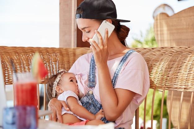 Adorabile giovane madre allegra allatta la piccola figlia, indossa un berretto nero alla moda e salopette di jeans, parla con il marito su smart phone, chiede di acquistare alcuni prodotti necessari, si siede all'aperto