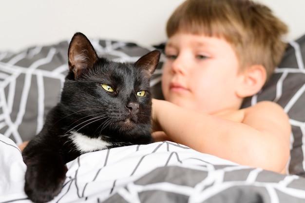 Adorabile giovane ragazzo coccole il suo gatto