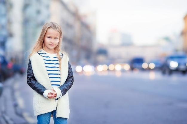 Adorabile moda bambina all'aperto in città europea