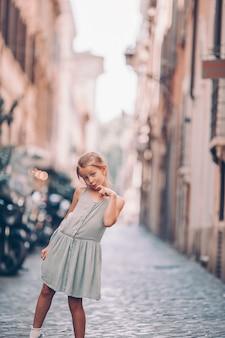 Adorabile moda bambina all'aperto nella città europea di roma