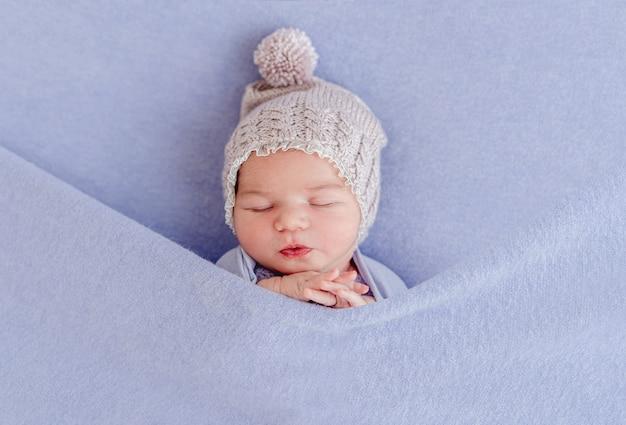 Adorabile neonato addormentato coperto di coperta