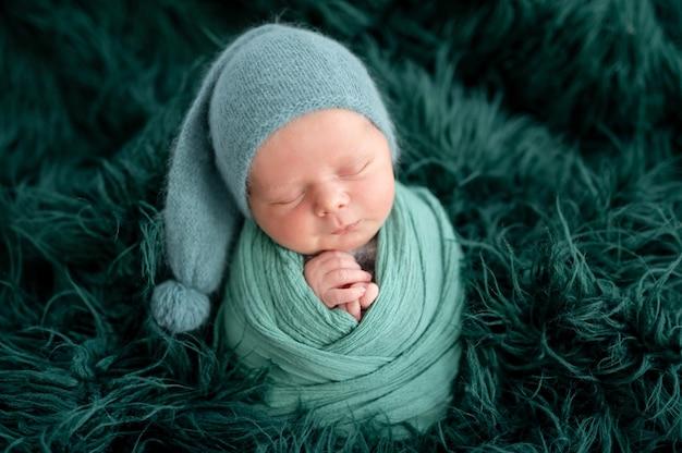 Adorabile neonato in cappello lavorato a maglia verde avvolto in una coperta