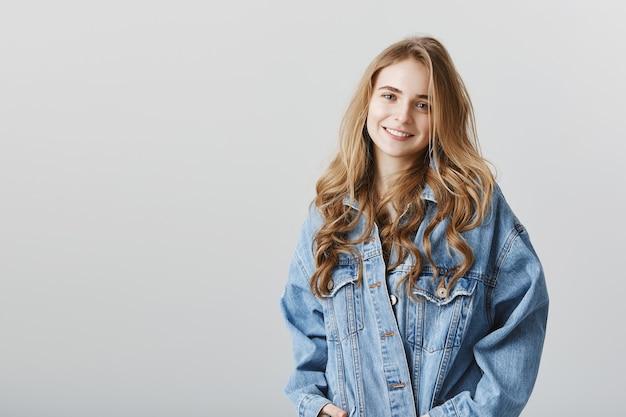 Adorabile ragazza bionda sorridente felice in giacca di jeans, in piedi sopra il muro grigio