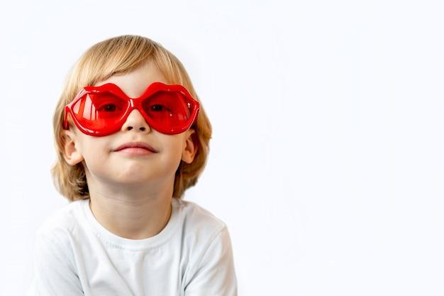 Adorabile ragazzino sorridente in camicia bianca in occhiali da sole rossi a forma di labbra