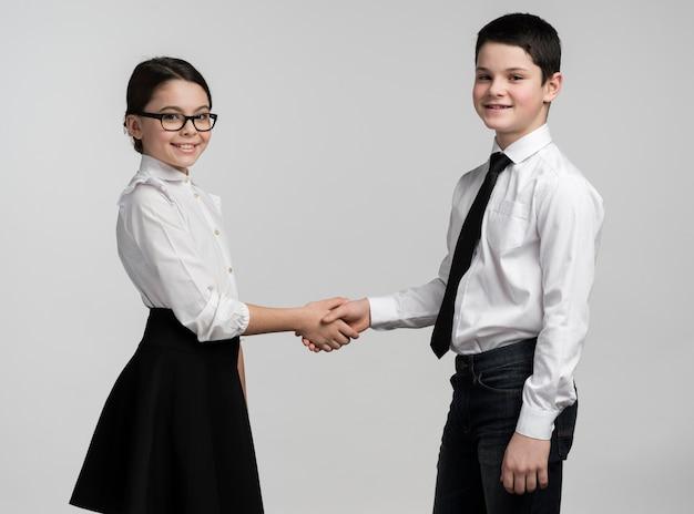 Adorabile ragazzo e ragazza si stringono la mano