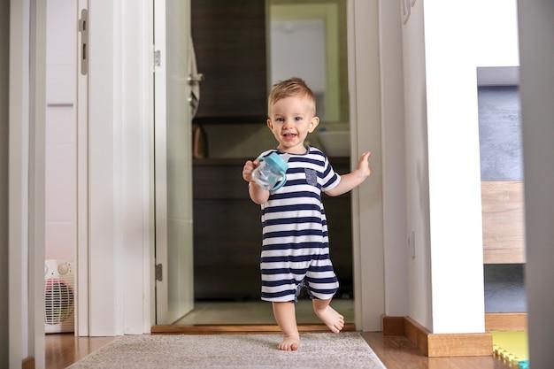 Adorabile ragazzo sorridente che tiene la sua bottiglia con acqua e fa i suoi primi passi.