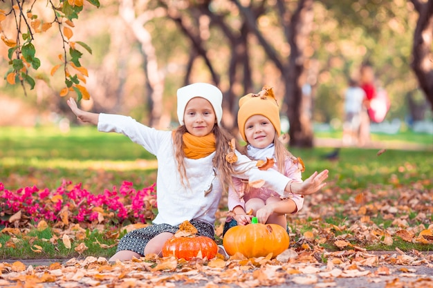 Adorabili bambine con zucca all'aperto in una calda giornata d'autunno.