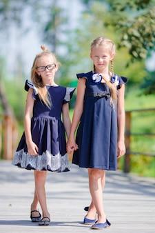 Adorabili bambine della scuola all'aperto in una calda giornata di settembre. di nuovo a scuola.