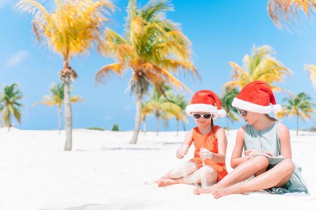 Adorabili bambine in cappelli di babbo natale durante le vacanze al mare si divertono insieme