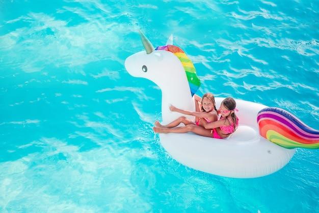 Adorabili bambine in piscina divertirsi durante le vacanze estive
