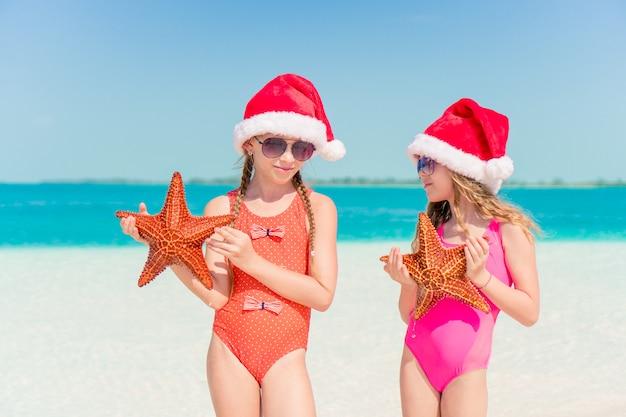 Adorabili bambine in vacanza di natale sulla spiaggia