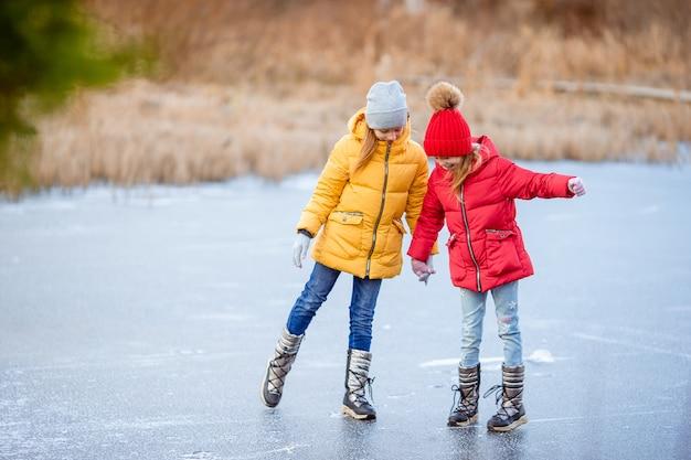 Adorabili bambine pattinaggio sulla pista di pattinaggio